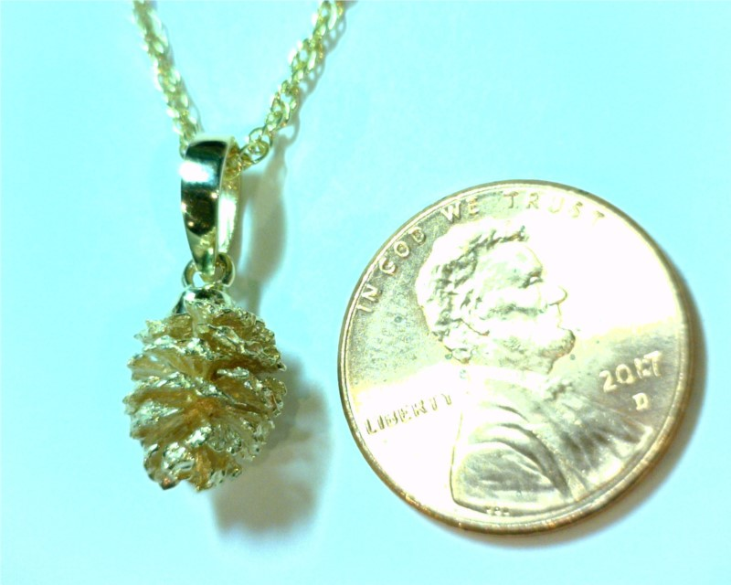 Charms - 14 Karat Yellow Gold Pine Cone Pendant Weighing 2.1 Grams. Comes on 18' Yellow Plated Display Chain that is highly recommended to be switched to a different chain for wearing.  All are slightly different from one another.   Please call/email or add comments upon checkout of what shape you would prefer. We find these Alder Pine Cones along the Truckee River and around Tahoe Streams.