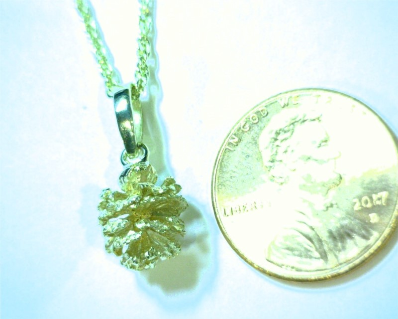 Charms - 14 Karat Yellow Gold Pine Cone Pendant Weighing 1.6 Grams. Comes on 18' Yellow Plated Display Chain that is highly recommended to be switched to a different chain for wearing.  All are slightly different from one another.   Please call/email or add comments upon checkout of what shape you would prefer. We find these Alder Pine Cones along the Truckee River and around Tahoe Streams.