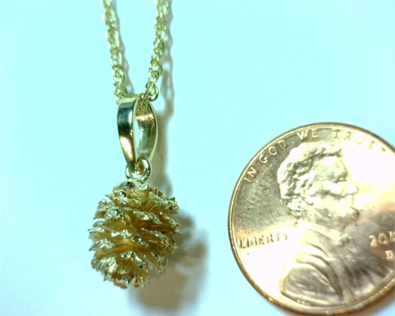 Charms - 14 Karat Yellow Gold Pine Cone Pendant Weighing 2.2 Grams. Comes on 18' Yellow Plated Display Chain that is highly recommended to be switched to a different chain for wearing.  All are slightly different from one another.   Please call/email or add comments upon checkout of what shape you would prefer. We find these Alder Pine Cones along the Truckee River and around Tahoe Streams.