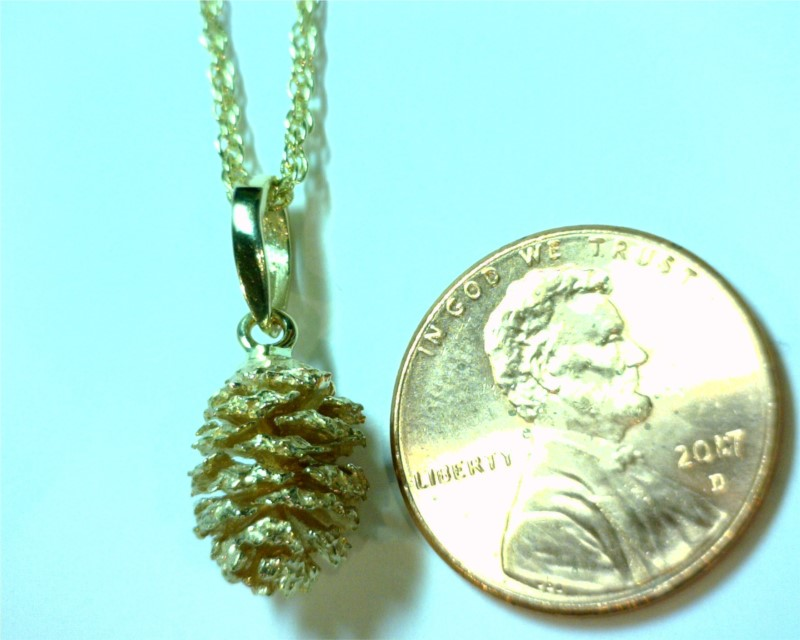 Charms - 14 Karat Yellow Gold Pine Cone Pendant Weighing 2.5 Grams. Comes on 18' Yellow Plated Display Chain that is highly recommended to be switched to a different chain for wearing.  All are slightly different from one another.   Please call/email or add comments upon checkout of what shape you would prefer. We find these Alder Pine Cones along the Truckee River and around Tahoe Streams.
