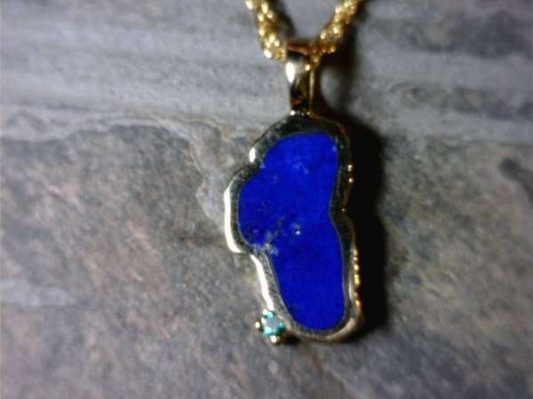 Large 14 Karat Yellow Gold Lapis Lake Tahoe Pendant with Emerald - Large 14 Karat Yellow Gold Lapis Lake Tahoe Pendant with a Round Chatham Emerald. Measures approximately seven eights an inch tall. Comes on an 18 inch yellow plated alloy display chain which is just for display & not for wearing. (It is recommended to switch onto a different chain for wear.)  All stones will vary in color tone & pattern.