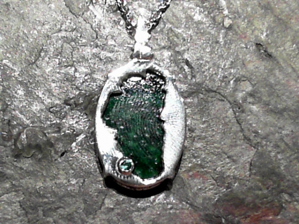 Maw Sit Sit Lake Tahoe Reversible Bear Pendant - Bluestone Exclusive Design. Sterling Silver Lake Tahoe/Bear Pendant(reversible) with Maw Sit Sit (center gemstone) & Lab Created Emerald.(where Emerald Bay is) Measures approximately 7/8 of an inch tall & 9/16 of an inch wide. ***Center Gemstones will vary in color & appearance.***