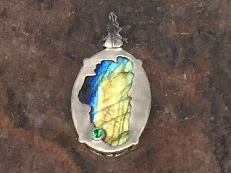 Labradorite Lake Tahoe Reversible Bear Pendant - Bluestone Exclusive Design. Sterling Silver Lake Tahoe/Bear Pendant(reversible) with Labradorite (center gemstone) & Lab Created Emerald.(where Emerald Bay is) Measures approximately 7/8 of an inch tall & 9/16 of an inch wide. ***Center Gemstones will vary in color & appearance.***