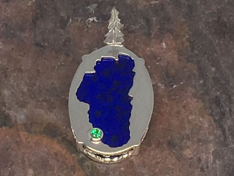 Lapis Lake Tahoe Bear Pendant - Bluestone Exclusive Design. Sterling Silver Lake Tahoe/Bear Pendant(reversible) with Lapis (center gemstone) & Lab Created Emerald.(where Emerald Bay is) Measures approximately 7/8 of an inch tall & 9/16 of an inch wide. ***Center Gemstones will vary in color & appearance.***